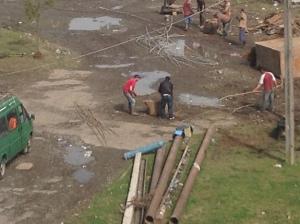 Men straightening out metal rebar.