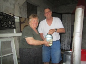 Tom and Bebia holding a 2 liter jug of ჭაჭა.