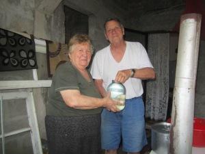 Tom and Bebia holding a 2 liter jug of ჭაჭა.